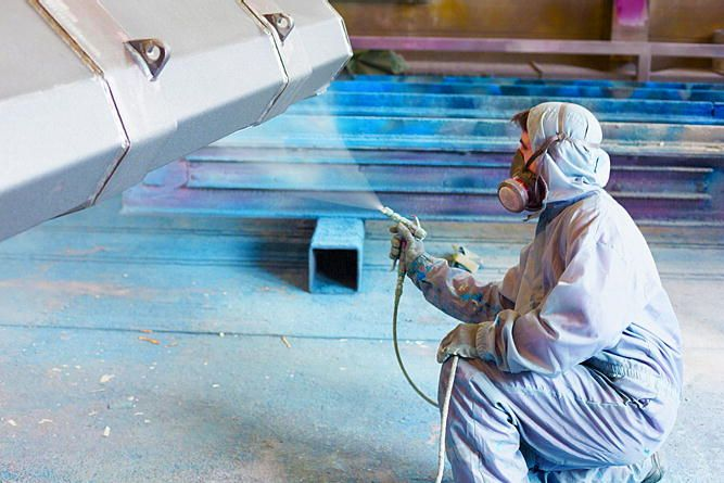 Industrial Painter painting a metal piece