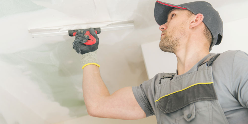 Man fixing drywall with putting drywall mud on with a putty knife