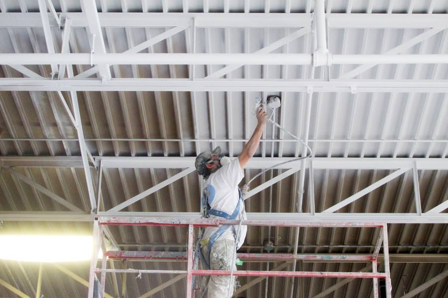 man painting the ceiling in a warehouse